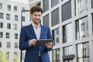 Smiling businessman in the city using tablet - DIGF04904
