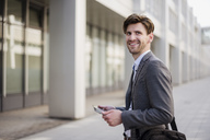 Smiling businessman in the city with bag and tablet - DIGF04934