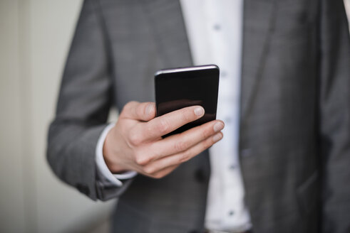 Close-up of businessman holding cell phone - DIGF04937