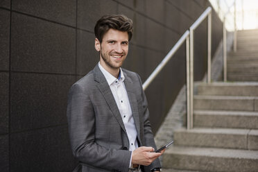Portrait of smiling businessman with cell phone on stairs - DIGF04940