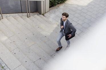 Smiling businessman with crossbody bag walking upstairs - DIGF04943