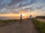 Portugal, Alentejo, senior man on e-bike at sunset - LAF02069