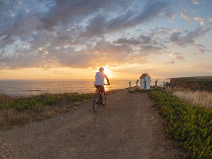 Portugal, Alentejo, senior man on e-bike at sunset - LAF02069