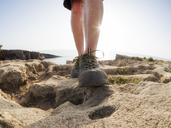 Senior man with hiker shoes standing on rock, against the sun - LAF02072