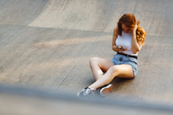 Redheaded woman using smartphone outdoors - GIOF04196