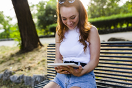 Laughing redheaded woman sitting on bench in park using digital tablet - GIOF04199