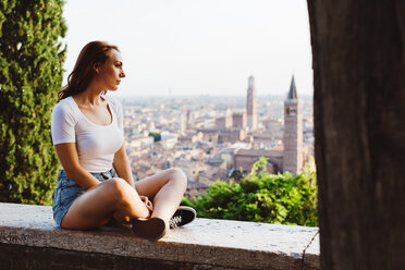 Italy, Verona, redheaded woman sitting on a wall looking at view - GIOF04217