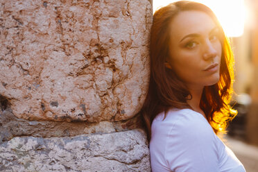 Portrait of redheaded woman leaning against wall at sunset - GIOF04220