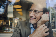 Mature businessman sitting in coffee shop, looking out of window - GUSF00991