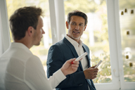 Mature businessman sharing his knowledge with younger colleague - GUSF00997