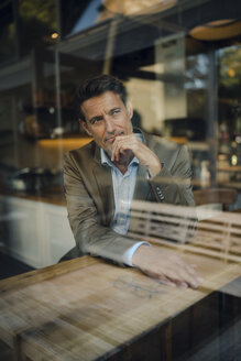 Mature businessman sitting in coffee shop, smiling - GUSF01030