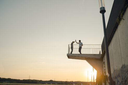 Two friends high-fiving at sunset, standing on observation platform - GUSF01036