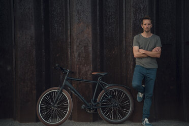 Man leaning aginst metal wall with arms crossed by bicycle - GUSF01048
