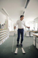 Businessman skiing in office - GUSF01084