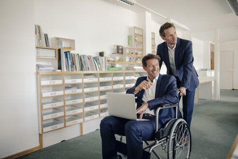 Colleague pushing businessman, sitting in wheelchai´r - GUSF01087
