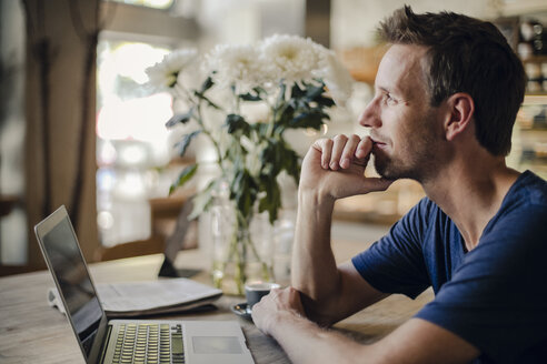 Mid adult man sitting in coffee shop, using laptop - GUSF01093