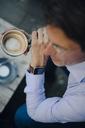 Mature businessman sitting in coffee shop, wearing smart watch - GUSF01105