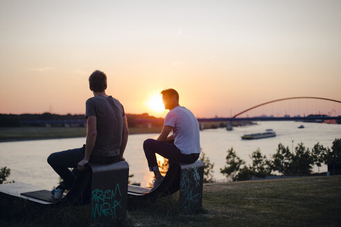Two friends watching sunset at the river - GUSF01123