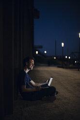 Mid adult man sitting cross-legged on ground, using laptop at night - GUSF01126
