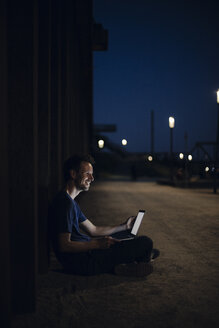 Mid adult man sitting cross-legged on ground, using laptop at night - GUSF01126