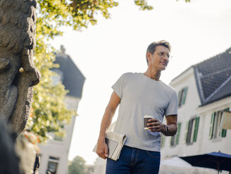 Mature man walking in he city with newspaper and digital tablet, drinking coffee - GUSF01153