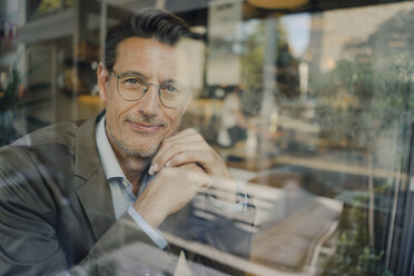 Mature businessman sitting in coffee shop, looking out of window - GUSF01162