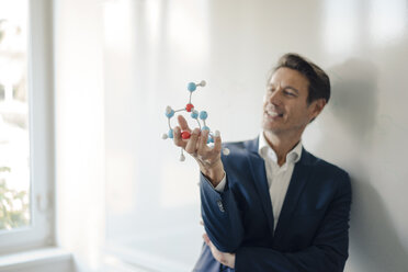 Successful businessman leaning on whiteboard, holding molecule model - GUSF01180