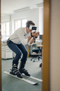 Businessman skiing in office, using VR glasses - GUSF01186