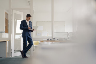 Businessman standing in office, using laptop - GUSF01189