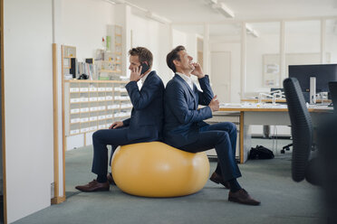 Two businessman checking smartphone with yellow fitness  ball in foreground - GUSF01198