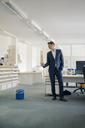 Businessman in office looking at wastepaper basket - GUSF01201