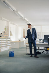 Businessman in office looking at wastepaper basket - GUSF01201