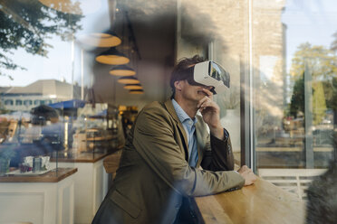 Mature businessman sitting in coffee shop, looking through VR glasses - GUSF01210