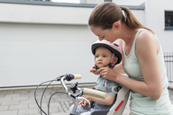 Mother and daughter, daughter wearing helmet sitting in children's seat - DIGF04954