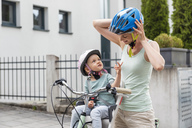 Mother and daughter wearing helmet, daughter sitting in children's seat - DIGF04957