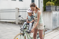 Mother and daughter riding bicycle, daughter wearing helmet sitting in children's seat - DIGF04960