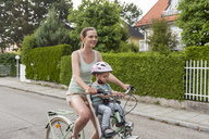 Mother and daughter riding bicycle, daughter wearing helmet sitting in children's seat - DIGF04963