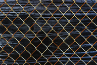 Close up of chainlink fence detail, stretched plastic behind. - MINF08680