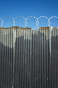 Worn corrugated metal fence, razor wire above. - MINF08683