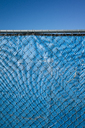 Blue fabric behind chainlink fence, blue sky above. - MINF08686