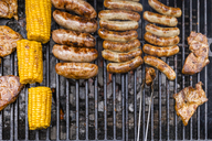 Different meat, maize and fried sausages on barbecue grill - TCF05635