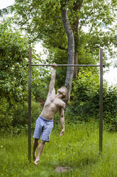 Athletic young man on high bar - TCF05638