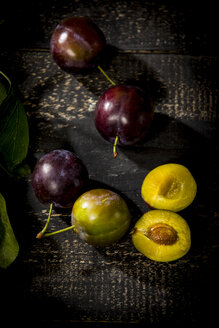 Whole and sliced plums on dark wood - MAEF12707