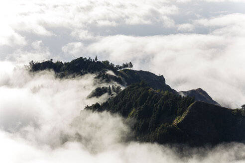 Aerial view of lush mountains on an island, surrounded by clouds. - MINF08780