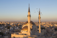 Cityscape at sunset, with mosque and minarets in the foreground. - MINF08831