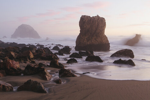 Seascape with breaking waves on rocks on sandy beach at dusk. - MINF08909