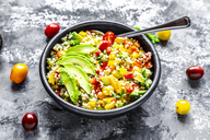 Bowl of bulgur salad with bell pepper, tomatoes, avocado, spring onion and parsley - SARF03919