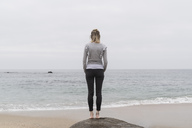 Back view of woman standing on the beach looking at distance - CHPF00503