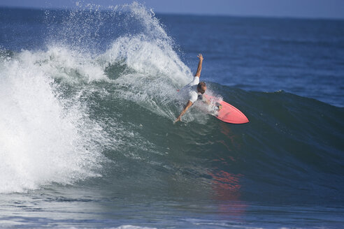A young man surfing at Rocky Point on the North Shore of Oahu, Hawaii. - AURF00674