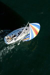 Aerial view of a sailing yacht with a colorful spinnaker cruising in Pittwater on the North Shore from Sydney, Australia. - AURF00776